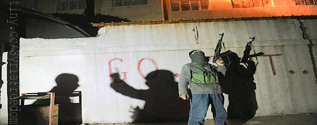 The shadows of armed Free Syrian Army rebels flicker across a wall at the entrance to the north Syrian city of Binnish