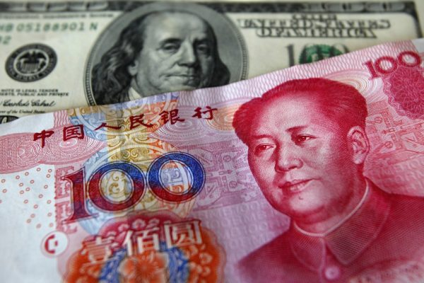 A yuan banknote is displayed next to a U.S. dollar banknote for the photographer at a money changer inside the Taoyuan International Airport, Taiwan