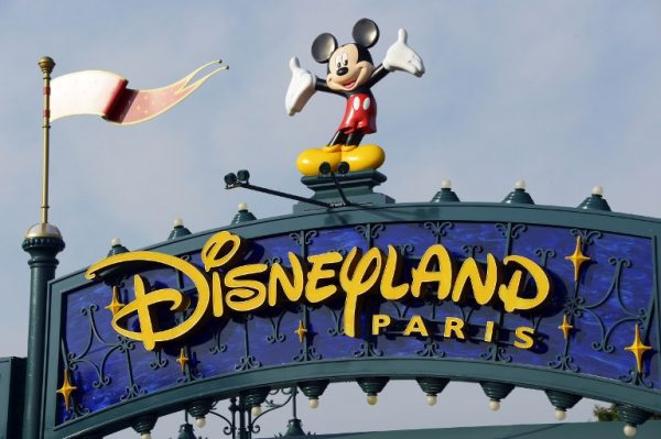 "(FILES) This file photo taken on August 13, 2015 shows a sign above the entrance at Disneyland Paris in Marne-la-Vallee. A man carrying two handguns, ammunition and a Koran was arrested on January 28, 2016 at a hotel in Disneyland Paris, police sources said. The man was ""detected upon his arrival at the Disneyland hotel where he had a reservation. Hotel security found two handguns, a Koran and ammunition on him"", said the source. / AFP / BERTRAND GUAY"