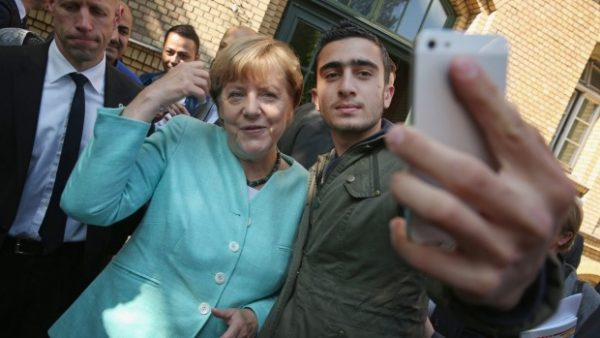 merkel poses with migrant