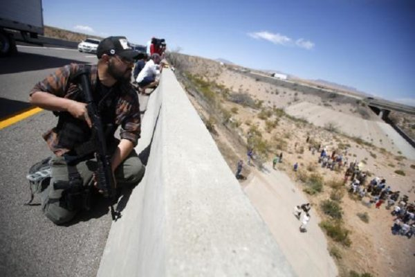 Eric Parker from central Idaho stands watch on a bridge with his weapon as protesters gather by the Bureau of Land Management's base camp, where cattle that were seized from rancher Cliven Bundy are being held, near Bunkerville, Nevada April 12, 2014. The U.S. Bureau of Land Management on Saturday said it had called off an effort to round up Bundy's herd of cattle that it had said were being illegally grazed in southern Nevada, citing concerns about safety. The conflict between Bundy and U.S. land managers had brought a team of armed federal rangers to Nevada to seize the 1,000 head of cattle. REUTERS/Jim Urquhart (UNITED STATES - Tags: ANIMALS CIVIL UNREST AGRICULTURE CRIME LAW TPX IMAGES OF THE DAY)