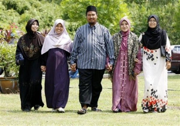 """In this Aug. 15, 2009 photo, polygamist Mohammad Inaamulillah Bin Ashaari, center, is shown with his four wives, from left, Rohaiza Esa, Ummu Habibah Raihaw , Nurul Azwa Mohd Ani,and Ummu Ammarah Asmis at the """"Ikhwan Polygamy Club Family Day"""" in Rawang, north of Kuala Lumpur, Malaysia. Polygamy is legal for Muslims in Malaysia, though not widespread. The Ashaari clan believes it should be. Last month, the sprawling family launched a Polygamy Club that seeks to promote plural marriages for what it says are noble aims, such as helping single mothers, prostitutes and older women find husbands. (AP Photo/Mark Baker)"""