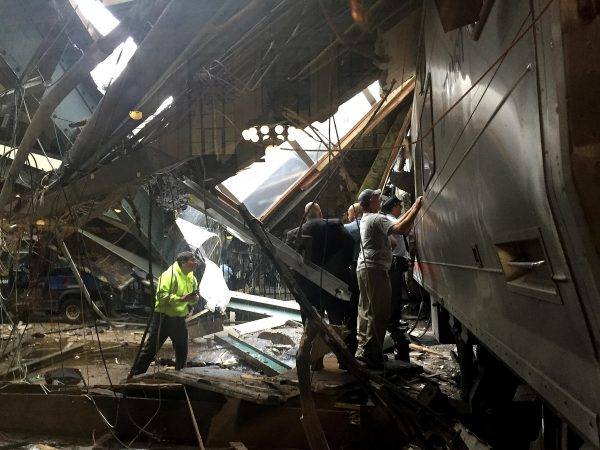 Personnel inspect the damage after a commuter train crashed into the station in Hoboken, N.J.