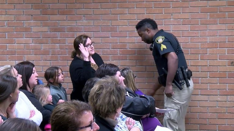 Teacher's rights violated after she was pushed to the floor and handcuffed for asking the school board questions